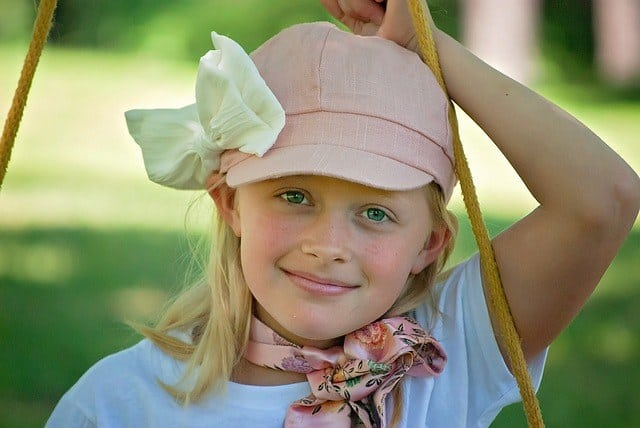 Picture of a young girl with green eyes and a hat.