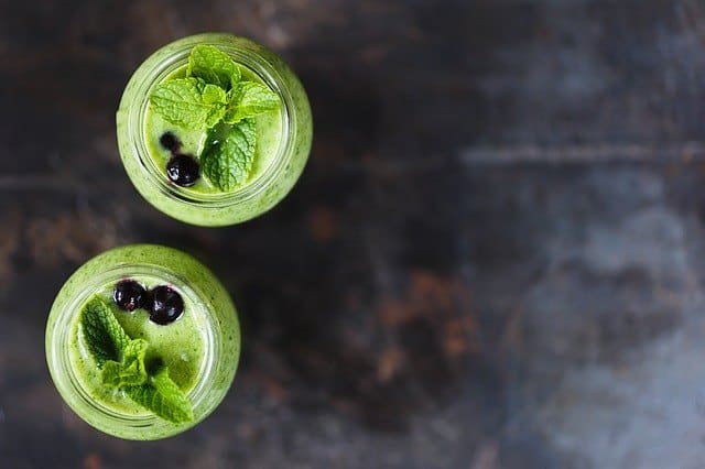 Picture of cucumber blueberry blast smoothie in two jars with two blueberries in each of it.