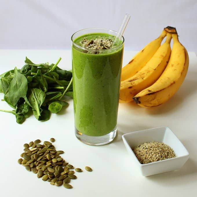 Picture of green protein power breakfast smoothie with straw in it. There are bananas on the right side, leaves on the left side, and pumpkin seeds on the front of the glass.