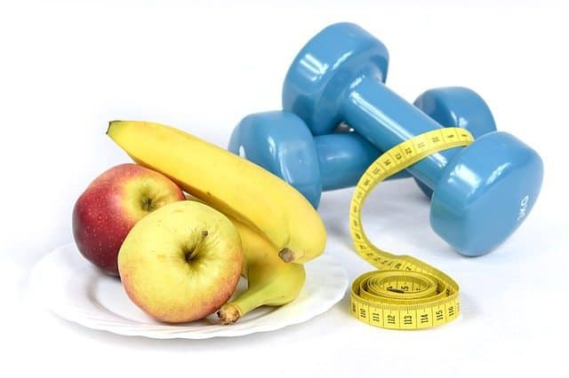 The picture of a plate with apples and bananas and weights on the right side.