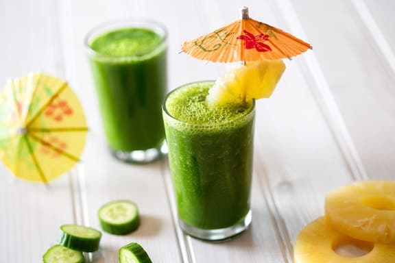 The picture of the kale pineapple smoothie with a twist in the two glasses and with a little umbrella in the both of them.
