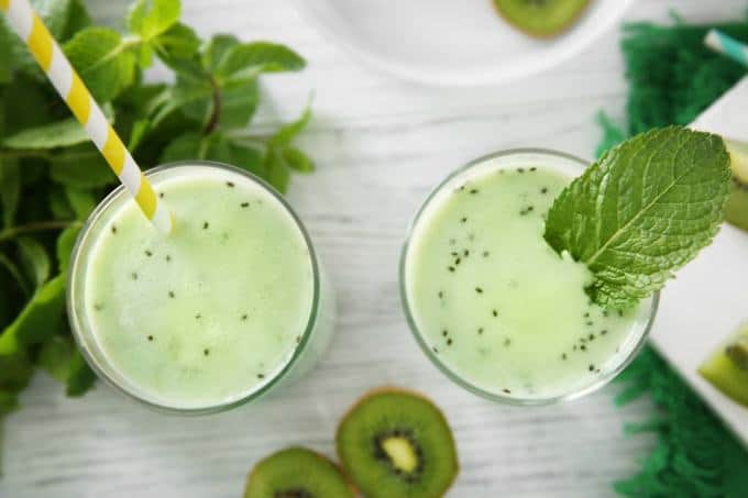The picture of green fat burning smoothie in two glasses. In the left glass, there is a straw and in the right glass, there is a leaf. Around glasses, there are a couple of leaves.