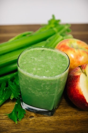 The picture of the kale apple smoothie with kale in the background with two apples on the side.