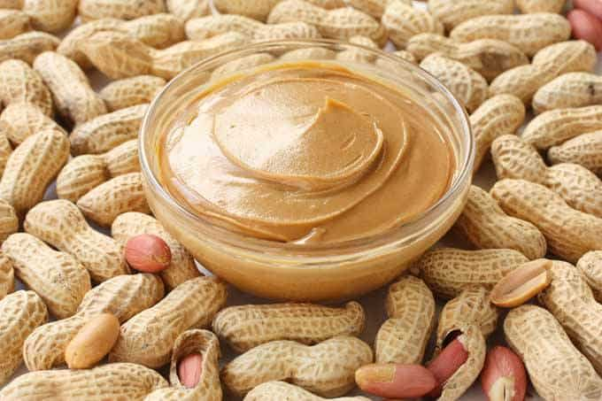 The picture of natural peanut butter in the bowl. All-around the bowl there are peanuts.
