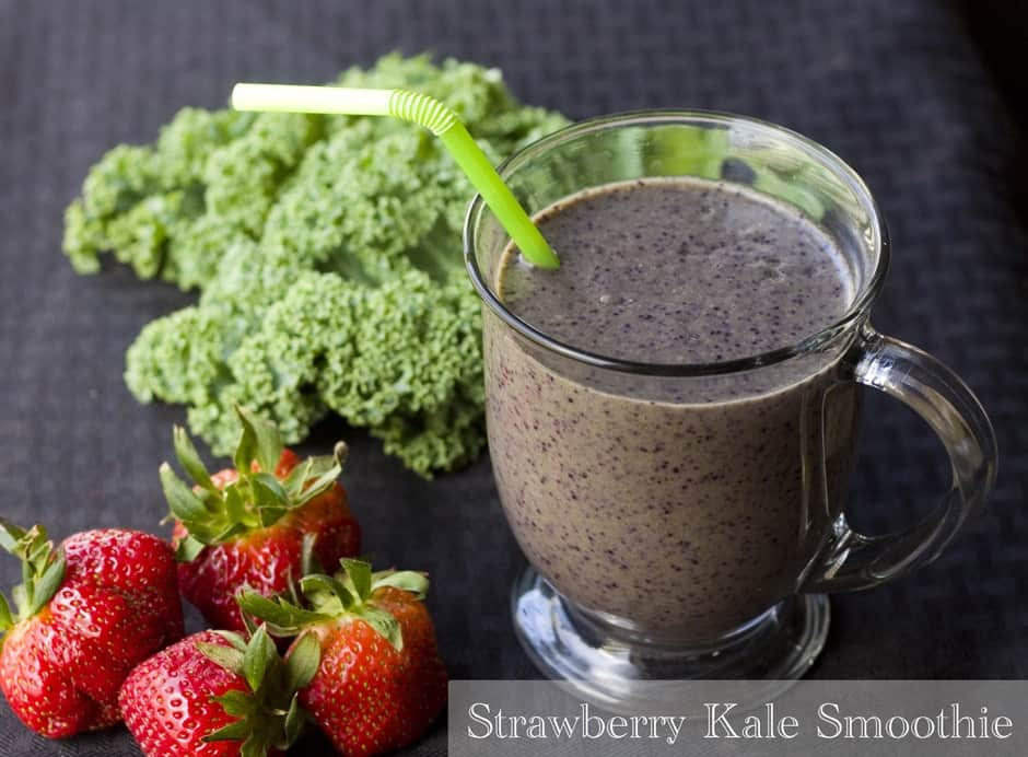 The picture of the kale strawberry smoothie in the glass with four strawberries on the left side and with kale on the upper left side form the glass.