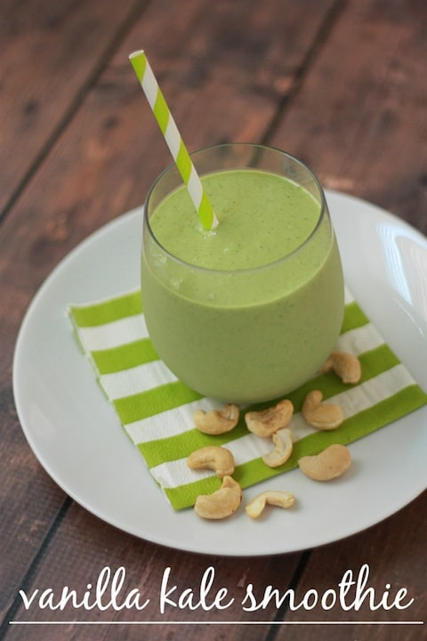 The picture of creamy vanilla kale smoothie in the glass with straw on the ceramic plate with Brazilian nuts around the glass.