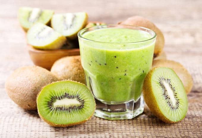 Picture of kiwi smoothie in a glass with two halves of kiwi from each side of the glass and with kiwis all around the glass.