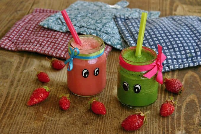 The picture of the kids fun with smoothies in the two jars with different color straws in it. There are strawberries around jars.