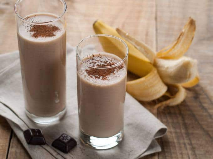 The picture of the healthy chocolate milkshake in a two glasses standing on the napkin with banana on the right side.