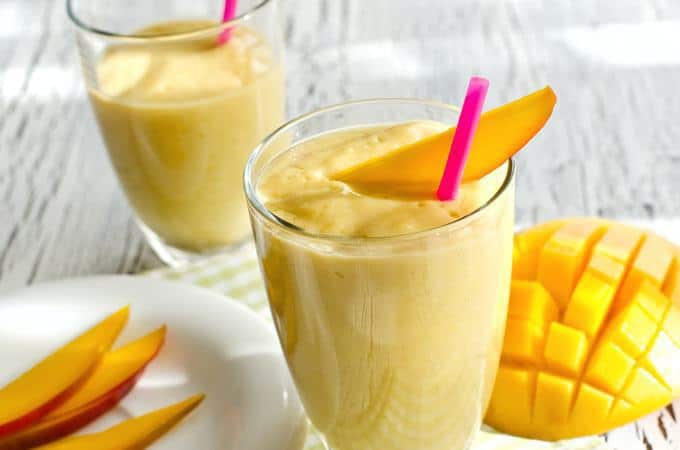 Picture of  two glasses of mango smoothies with straw in both glasses.
