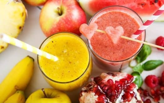 The picture of the two smoothies in the two separate glasses side by side. The left smoothie is a yellow color with straw in it. The right smoothie is a red-pink color withheart-shaped watermelonplaced on the stick. In the top left corner of the picture, there is a red apple, and on the bottom left corner, there is a yellow apple. On the bottom right corner, there is apomegranate.