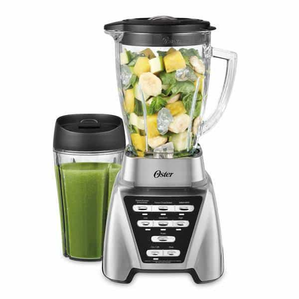 The picture of Oster Pro 1200 blender full of vegetables ready to be blended. On the left side of the blender there is glass of smoothie.