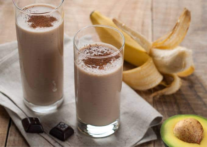 The picture of choco-cado smoothie in two glasses standing on the napkin and with banana on the right side.