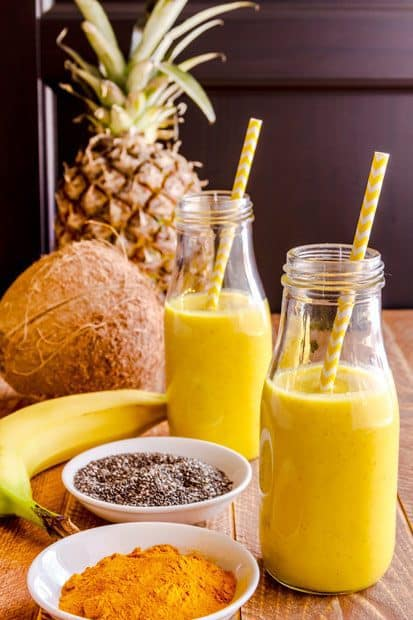 Picture of  pineapple coconut oatmeal smoothie in two bottle glasses with straws in both of them with annas in the background, coconut from the left side, banana as well