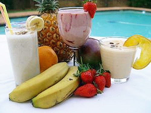 Picture of smoothies in three glasses with ananas, orange, banana, strawberry, and mango around it.
