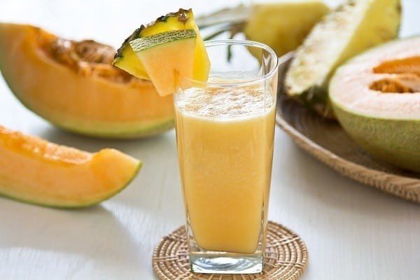 The picture of coconut water pineapple smoothie in the glass with a slice of pineapple placed on the edge of the glass. There are sliced pineapples around the glass.
