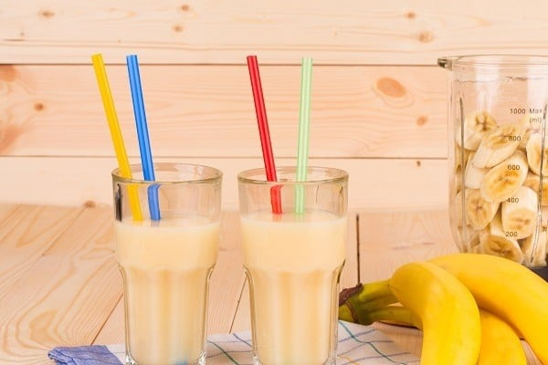 Picture of banana juice in the two glasses with a pair of straws in each glass. Blender and three bananas are on the right side of the glass.