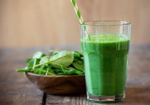 The picture of spinach smoothie in the glass with staw in it. On the right side of the glass, there is a bowl full of spinach leaves. Everything is standing on the wooden table.