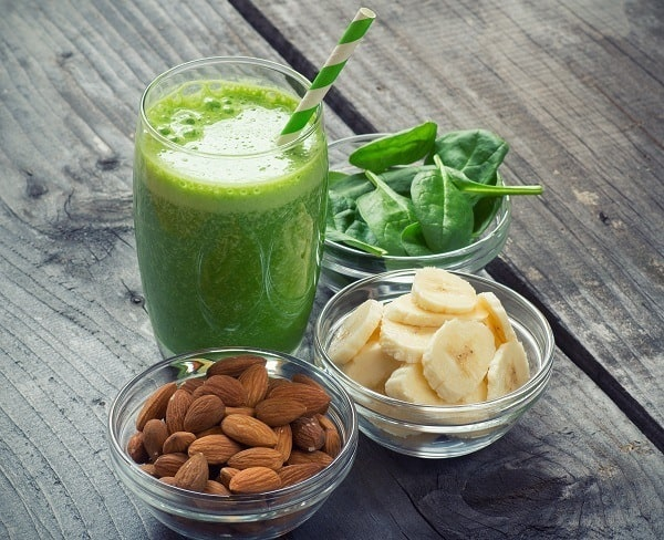 The picture of a spinach and banana smoothie in the glass with a straw in it. There are three bowls around the glass. In the first bowl is almond, in the second is sliced banana, in the third is leaves of spinach.