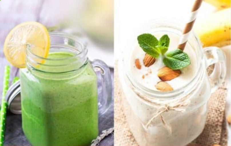 The picture of two smoothies. On the left side is a green smoothie in the jar with straw in it, and a slice of lemon placed on the edge of the jar. On the right side of the picture is a white smoothie in a jar with almonds on the top of the smoothieand a stawin it.