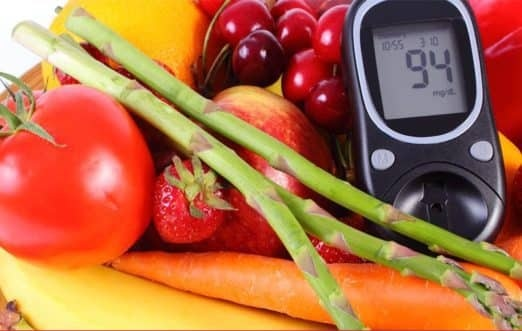 The picture of the bunch of fruits and vegetables with a diabetic calculator on the right side. On the picture, there are strawberries, tomato, cherries, carrot, oranges.