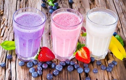 The picture of three different smoothies in three different glasses side by side. The left smoothie is a purple color, the middle one is pink color, and the right one is white color. All three smoothies are standingon the wooden table. Around smoothies are blueberries, two sliced strawberries, and one banana on the right side of the third smoothie.