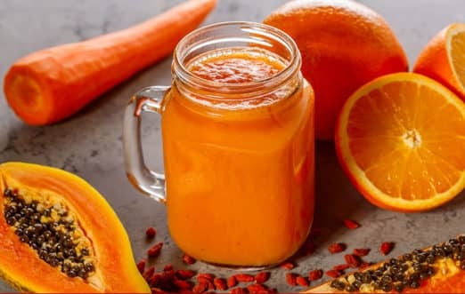 The picture of orange and carrot smoothie in a jar. On the right side, behind the jar, there are two sliced oranges and one orange. On the left side of a jar, there is a piled carrot, and on the bottom left side of a jar, there is sliced avocado.