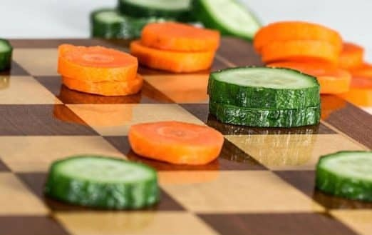 The picture of the sliced cucumber and carrot on the chessboard.